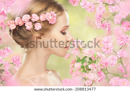 Beauty face of young beautiful woman with pink flowers in her hair - stock photo