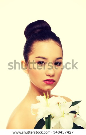 Beauty face of young woman with lily flower.  - stock photo