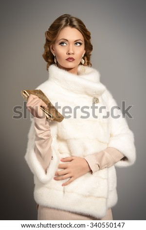 Beauty, fashion and luxury concept. Elegant young woman with evening make-up and hairstyle posing in beautiful dress and white mink fur jacket. Jewellery. Studio shot. - stock photo