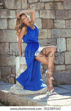 Beauty Fashion girl model in blue dress posing on part of column against brick wall. Summer slim lady portrait.  - stock photo