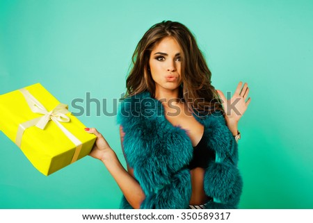 Beauty Fashion Model Girl in Blue Mink Fur Coat. Beautiful Luxury Winter Woman.crazy hipster girl with funny hairstyle and vivid faux fur coat,emotional teen woman,impressed of her christmas present  - stock photo