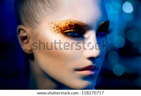Beauty Fashion Model Girl with Holiday Leopard Makeup. Yellow Wild Cat Eyes Make-up Eyeshadow. Beautiful Woman Face with Perfect skin. Animal Make up. Blue Abstract Bokeh Background - stock photo