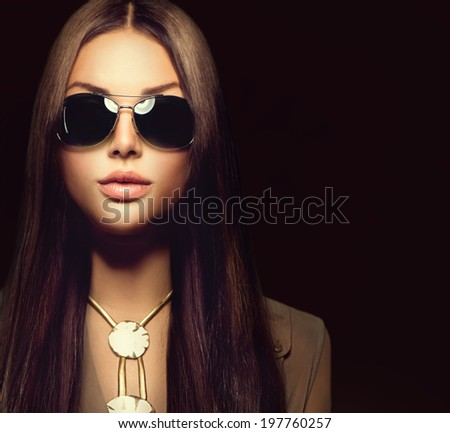Beauty Fashion model girl with long brown hair wearing stylish sunglasses. Sexy woman portrait over black background - stock photo