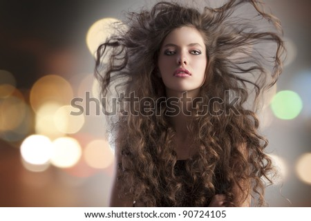 beauty fashion portrait of a very young cute alluring brunette with long curly hair with hairstyle flying in the wind and city lights - stock photo