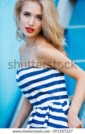 beauty fashion portrait of blonde woman with red lips and stripped dress. Fashion portrait. Smiling blonde woman in fashionable look. Sea style. On blue background. Style and hot girl outdoor. - stock photo