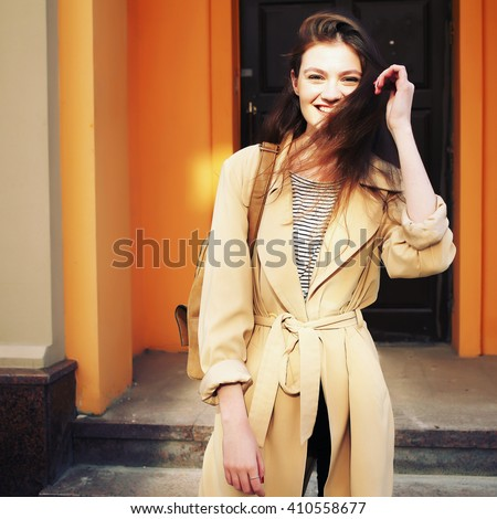 Beauty fashion portrait of brunette woman with natural make-up and leather backpack wearing long beige trench coat. Glamour sensual young girl in fashionable look. On city street background, outdoors. - stock photo