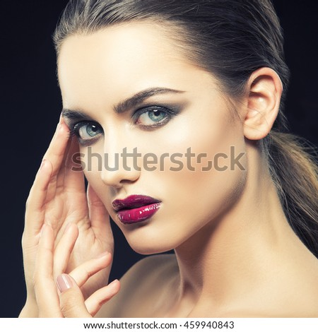 Beauty fashion portrait of caucasian brunette woman with wet red lipstick and arms touching face. Isolated on black background. Toned - stock photo