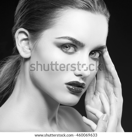 Beauty fashion portrait of caucasian brunette woman with wet red lipstick and arms touching face. Isolated on black background. Black and white - stock photo