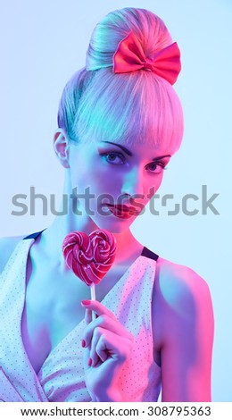 Beauty fashion portrait of sexy woman with heart shaped lollipop.  Sensual attractive playful blond girl. Luxury makeup, lips. Pin up hairstyle with fringe, pink bow. Colour creative toned, pink, blue - stock photo