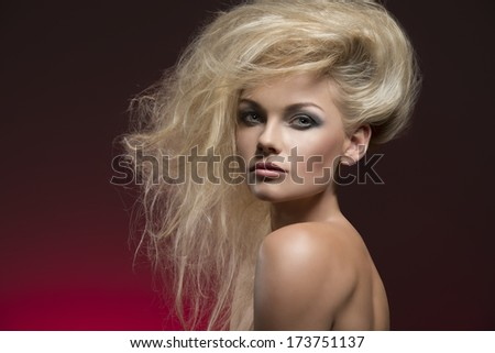 beauty fashion shoot of sexy woman with naked shoulders, charming bushy creative hair-style and cute make-up  - stock photo