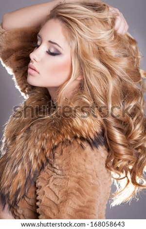 Beauty fashion woman in fur coat winter. Winter Girl in Luxury Fur Coat and evening makeup. Jewelry and Fashion elegant lady. Blond woman with long curly healthy hair. Studio. - stock photo