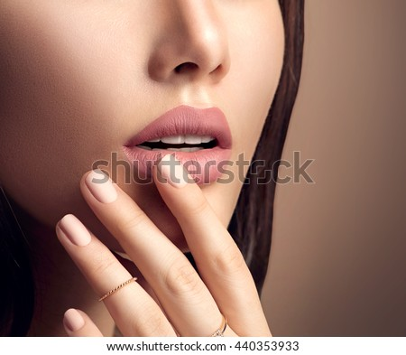 Beauty Fashion woman lips with natural Makeup and beige Nail polish. Matte lipstick and nails. Beauty girl face close up. Nude Colors. Sexy lips, Manicure, Make up - stock photo