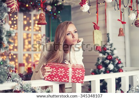 Beauty fashion woman with Christmas gift box, new year tree background - stock photo