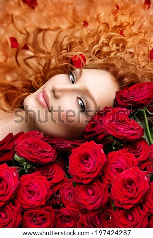 Beauty Fashion Woman with long curly red hair and beautiful red roses bouquet. Hairstyle with flowers. Beauty model girl lying on beautiful roses.  Wavy healthy hair. Permed hair - stock photo