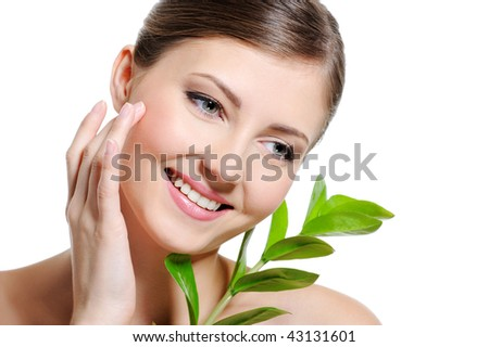 Beauty  female face with a clean purity skin touching cheek by her index finger - stock photo
