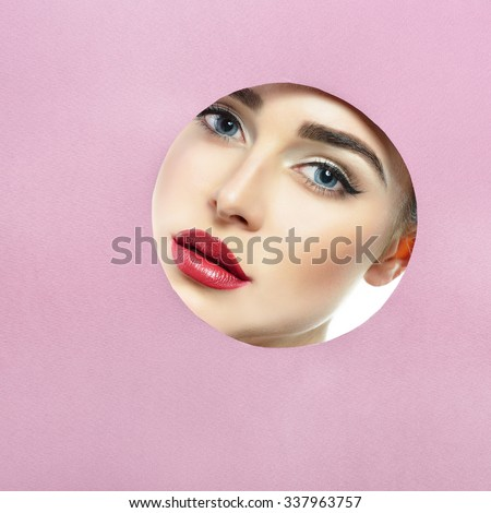 Beauty female portait. Young beautiful woman look out of circle in purple paper. Girl's face in round paper frame with copyspace for your message - stock photo