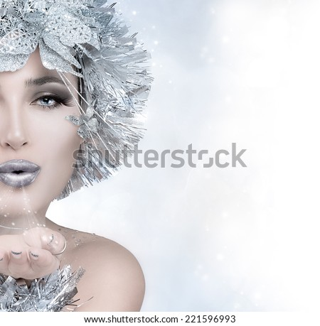 Beauty festive fashion. Christmas girl sending a kiss. Magic winter woman with silver stylism. Vogue style model blowing her hand. Sending good wishes. Half face portrait with copy space for text - stock photo
