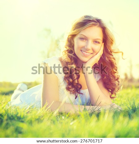 Beauty Fresh Romantic Girl lying on summer field Outdoors. Nature. Beautiful Model young Woman with long curly hair Smiling. Cute Teenage Girl lying on grass. Grassland. Allergy free. Sunshine - stock photo