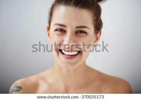 Beauty girl face Portrait. Beautiful model woman perfect fresh clean skin. Female looking at camera and smiling. Youth and skin care concept. Isolated on background - stock photo