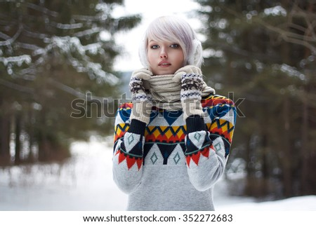 Beauty girl in winter forest. beautiful young Woman in fashionable woolen pullover and scarf - stock photo