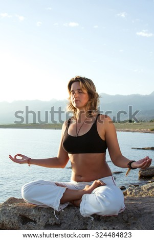 beauty girl in yoga pose on beach - stock photo