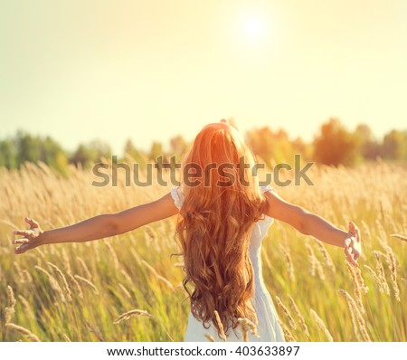 Beauty Girl Outdoors enjoying nature. Beautiful Teenage Model girl in white dress running on the Spring Field, Raising hands in Sun Light. - stock photo