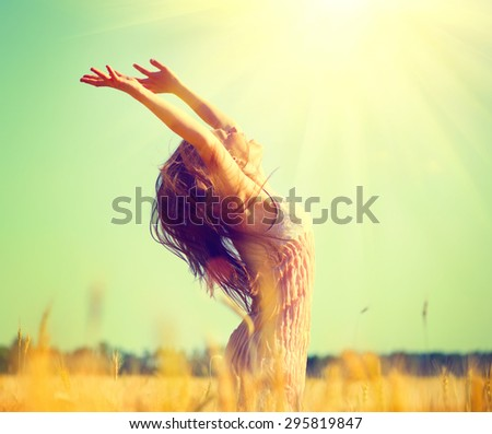 Beauty Girl Outdoors enjoying nature on wheat field. Beautiful Teenage Model girl with long hair raising hands on golden Field, Sun Light. Glow Sun. Free Happy Woman. Toned in warm colors - stock photo
