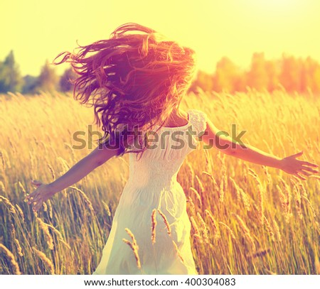 Beauty Girl Outdoors enjoying nature, raising hands. Beautiful Teenage Model girl with long healthy blowing hair running on the Spring Field, Sun Light Glow Sun. Free Happy Woman. Toned in warm colors - stock photo