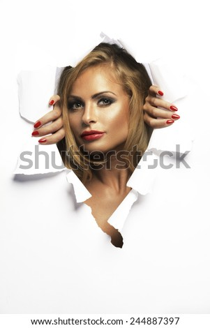 Beauty girl peeking out of the hole  - stock photo