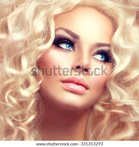 Beauty Girl With Healthy Long Curly Hair. Blonde Woman Portrait with blue eyes. Blond Wavy permed Hair and bright makeup, vivid make-up, smoky eyes and false eyelashes. Holiday make up. Perfect skin - stock photo