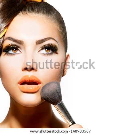 Beauty Girl with Makeup Brush. Bright Holiday Make-up for Brunette Woman with Brown Eyes. Orange and Yellow Make up. Beautiful Face. Makeover. Perfect Skin. Applying Makeup  - stock photo
