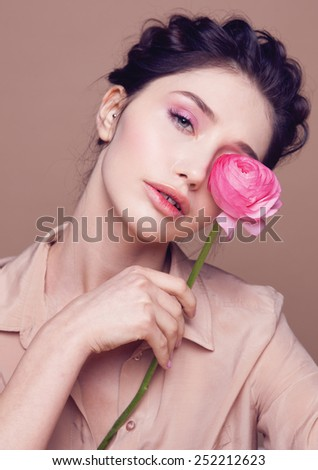 Beauty Girl With Pink Flower in her hand,Beautiful Model Woman Face. Perfect Skin. Professional Make-up.Makeup. Spring look, beige background - stock photo
