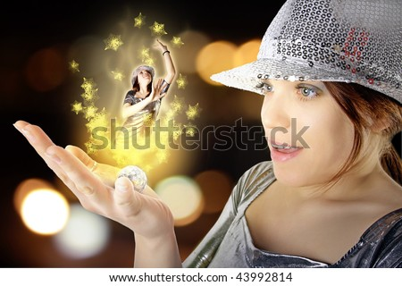 Beauty girl with silver hat holding magic disco ball with light effect and girl dancer in her palm - stock photo