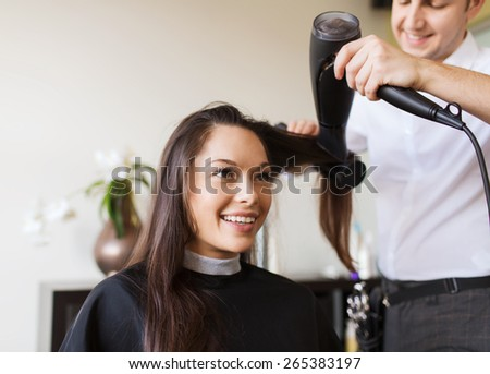 beauty, hairstyle and people concept - happy young woman and hairdresser with fan making hot styling at hair salon - stock photo