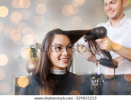 beauty, hairstyle and people concept - happy young woman and hairdresser with fan making hot styling at hair salon over holidays lights - stock photo