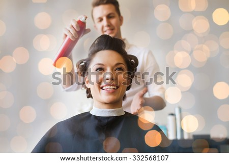 beauty, hairstyle and people concept - happy young woman with hairdresser with hair spray fixating hairdo at salon over holidays lights - stock photo