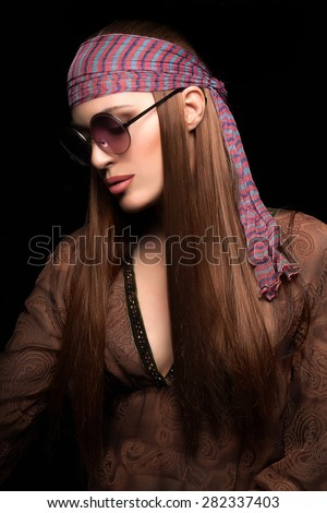 Beauty Hairstyle Fashion. Pretty Young Hippie Woman with Healthy Long Brown Straight Hair, Wearing Brown Dress and Sunglasses, Isolated on Black Background. - stock photo