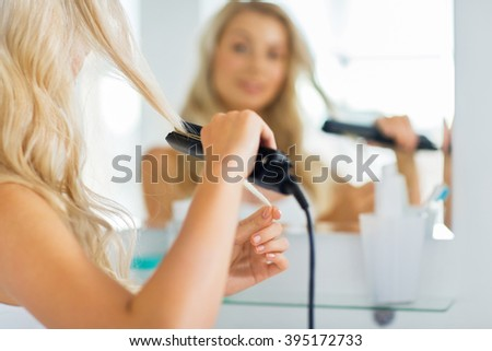 beauty, hairstyle, morning and people concept - close up of young woman with styling iron straightening her hair and looking to mirror at home bathroom - stock photo