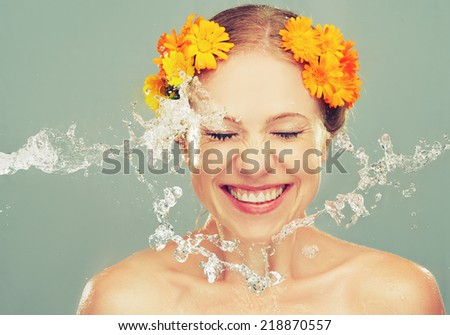 beauty happy laughing girl with splashes of water and yellow flowers - stock photo