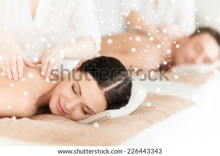 beauty, health, holidays, people and spa concept - happy couple with closed eyes lying getting back massage in spa salon - stock photo