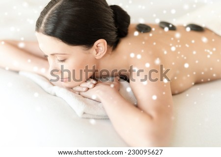beauty, health, people and spa concept - beautiful woman in spa salon getting hot stones massage - stock photo