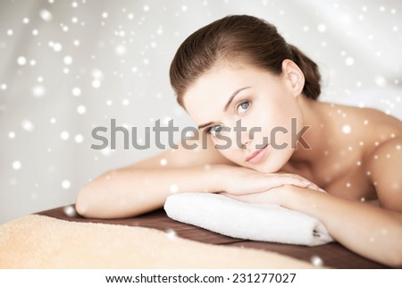 beauty, health, people and spa concept - beautiful young woman in spa salon lying on the massage desk - stock photo
