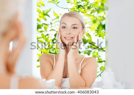 beauty, hygiene, morning and people concept - smiling young woman looking to mirror at home bathroom over green natural background - stock photo