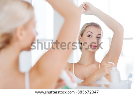 beauty, hygiene, morning and people concept - young woman applying antiperspirant or stick deodorant and looking to mirror at home bathroom - stock photo