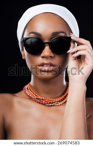Beauty in style. Beautiful African woman wearing a headscarf and adjusting her sunglasses while standing against black background - stock photo