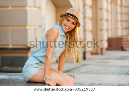 Beauty in the city. Cheerful young woman looking at camera and smiling while sitting outdoors - stock photo