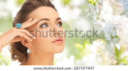 beauty, jewelry, people and accessories concept - close up of woman face with cocktail ring on hand and earrings over summer garden and cherry blossom background - stock photo