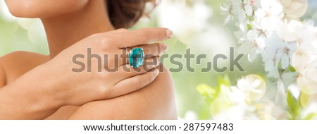beauty, jewelry, people and accessories concept - close up of woman with cocktail ring on hand over summer garden and cherry blossom background - stock photo