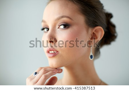 beauty, jewelry, wedding accessories, people and luxury concept - close up of beautiful asian woman or bride with earring and finger ring - stock photo