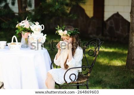 Beauty kid girl in flower wreath having tea in the garden - stock photo